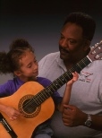 Father provoding support for daughter learning to play guitar