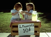 Two little girld selling lemonade at a stand while sampling their wares
