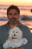 Mark holding his poodle friend, Tessie, at a sunset beach in Cambria, California