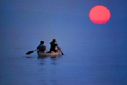 Two people paddling a canoe in deep blue water with a strong red sun in the background